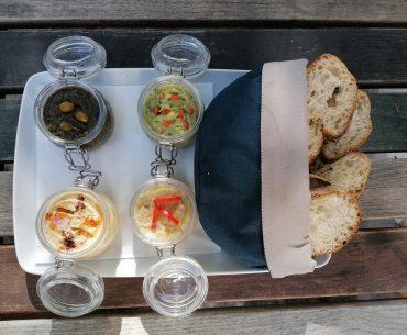 Un basarabean din Chișinău stabilit în București oferă clienților pub-ului său salată de humus, preparată cu năut din Piața Obor, după sfaturile unui bucătar american